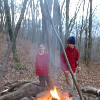 two scouts poking the campfire