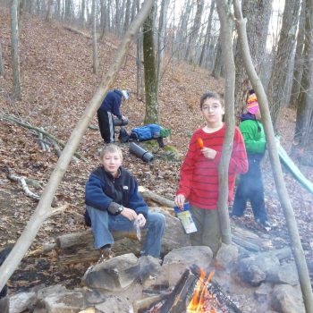 scouts eating around a campfire
