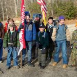 group of scouts in winter gear holding flags