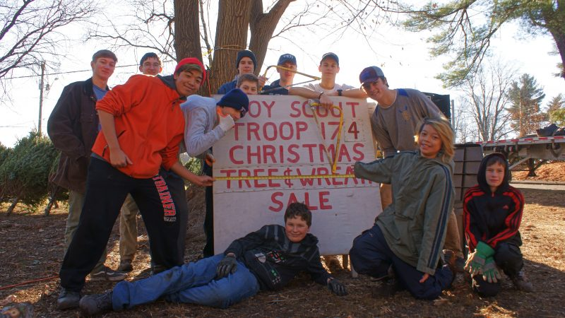 Boys surrounding a sign that says Boy Scout Troop 174 Christmas Tree & Wreath Sale